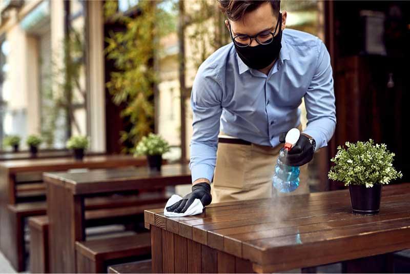 camarero limpiando mesa